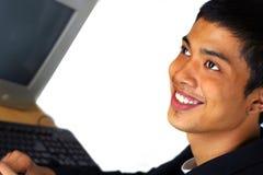 Mannlächeln an der Frontseite des Computers Stockfotos