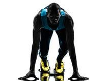 Mannläufersprinter auf Startblöcken   Schattenbild Stockfotos