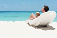 Mannlüge auf Ruhesessel mit Kokosnuss. Freizeitbetätigung auf Strand.  Mann Stockfotografie
