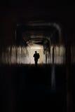 Mannlack-läufer entlang einem dunklen Flur Lizenzfreie Stockbilder