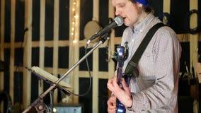 Mannlead-gitarrist, der Gitarre und Lied singen spielt stock footage