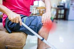 Mannleiden von den Knieschmerz und Spazierstock, der auf Sofa sitzt lizenzfreie stockfotografie