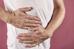 Mannleiden von den Schmerz in seiner Seite Rosa Hintergrund Magen, Leberschmerz, Pankreas, Nieren lizenzfreie stockfotografie