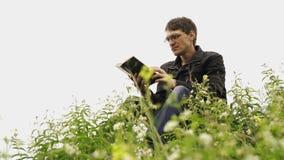 Mannlesebuch auf dem grünen hügeligen Gebiet Seitenansicht des jungen gut aussehenden Mannes in den Gläsern und im warmen Jackenl stock video