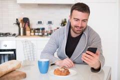 Mannlesenachrichten an seinem Handy morgens Stockfotos