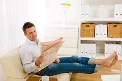 Mannlesezeitung auf Couch Lizenzfreies Stockfoto