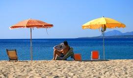 Mannlesezeitung auf Strand Stockbilder