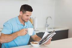 Mannlesezeitung beim Trinken des Kaffees Stockbild