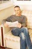 Mannlesezeitung von mittlerem Alter zu Hause Lizenzfreies Stockbild