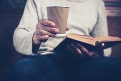 Mannlesung und Trinken von der Papierschale Stockfoto