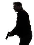 Mannmörderpolizist, der Gewehrschattenbild hält Stockfoto