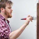Mannmalereihausmauer mit Bürste DIY-Heimwerken Stockfoto