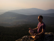 Mannmeditation auf einem Felsen Stockfotografie