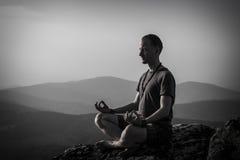 Mannmeditation auf einem Felsen Stockbilder