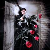 Mannmörder mit Gewehr und roten Rosen Stockfotos
