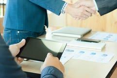 Mannnotenschwarztablette mit Händedruckhintergrund Lizenzfreies Stockfoto