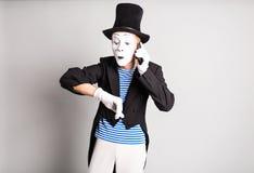 Mannpantomime, der an seinem Handy spricht Konzept des Aprilscherzes Tages Stockfotografie