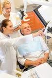 Mannpatient an der zahnmedizinischen Abfragezahnarztchirurgie Stockbilder