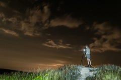 Mannphotograph macht Fotos einer Nachtlandschaft auf einem hohen Hügel Stockfoto