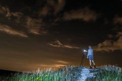 Mannphotograph macht Fotos einer Nachtlandschaft auf einem hohen Hügel stockfotos