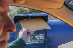 Mannpostsendungs-Steuererklärung - großer Umschlag am Antrieb durch Briefkasten mit dem Gesicht verwischt - selektiver Fokus lizenzfreies stockfoto