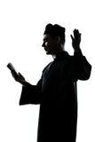 Mannpriesterschattenbild-Lesebibel Stockfoto