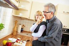 Mannprobierenerdbeere in der Küche stockbilder