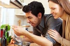 Mannprobierensuppe in der Küche Stockfoto
