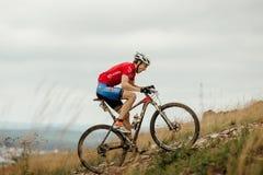 Mannradfahrermountainbiker, der aufwärts reitet lizenzfreies stockfoto