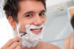Mannrasuren mit einer Rasierklinge und einem Rasierschau Lizenzfreies Stockfoto