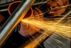 Mannreibender Stahlschläuche mit der pneumatischen Schleifscheibe, die Funken duscht lizenzfreie stockbilder