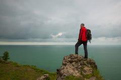 Mannreisender steht auf einer Klippe vor dem Meer Stockfotos