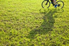 Mannreiten auf einer Wiese mit Schatten Stockfotografie
