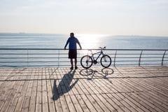 Mannreiten im Hintergrund des frühen Morgens See Stockfoto