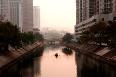 Mannruderboot durch Stadt Stockfotografie