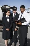 Mannschaftsmitglieder, die Berichte am Flugplatz besprechen Stockfotos
