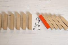 Mannschattenbild, das Domino-Effekt auf dunklem Hintergrund oder Tafel stoppt lizenzfreie stockfotografie