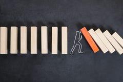 Mannschattenbild, das Domino-Effekt auf dunklem Hintergrund oder Tafel stoppt stockbild