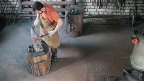 Mannschmied in der Schmiede stellt Metallwerkzeuge - Draufsicht her stock video footage
