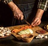 Mannschnittkarotten Nahe rohem Gemüse r Rustikales Artfoto lizenzfreie stockfotos