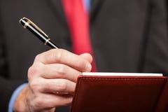 Mannschreiben auf seiner Tagesordnung Stockbild
