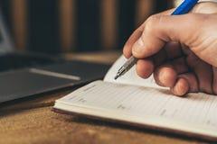 Mannschreiben in einem Notizbuch, Planungsmünder mit Laptop im Hintergrund lizenzfreie stockbilder