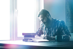 Mannschreiben mit Stift- und Lesebüchern Lizenzfreie Stockfotografie