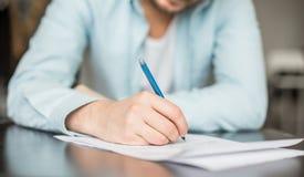 Mannschreiben am Schreibtisch Stockfotos