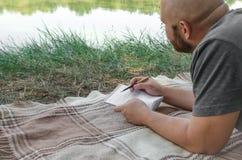 Mannschreiben in seinem Notizbuch im Wald lizenzfreies stockfoto