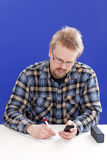 Mannschreiben an seinem Schreibtisch Stockfotos