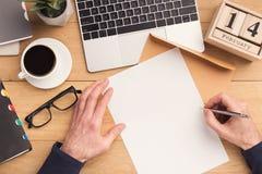 Mannschreibensbuchstabe am Arbeitsplatz beim Arbeiten Lizenzfreies Stockbild