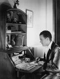 Mannschreibensbuchstabe am Schreibtisch Stockfotografie