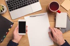 Mannschreibensbuchstabe und Holding Smartphone Stockfotos