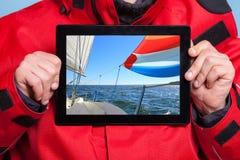 Mannseemann, der Yachtboot auf Tablette zeigt. Segeln Lizenzfreie Stockfotografie